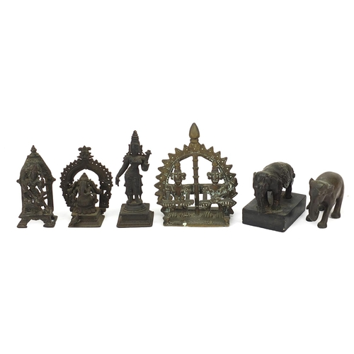 215 - Indian bronzes including votive figures and two elephants, one raised on a rectangular black slate b...
