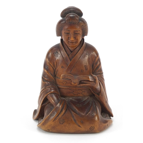 51 - Japanese erotic carved hardwood okimono of a lady kneeling down reading a book, character mark to th...