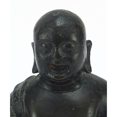 112 - Chino Tibetan patinated bronze figure of Buddha sitting on a carved hardwood base, 18cm high