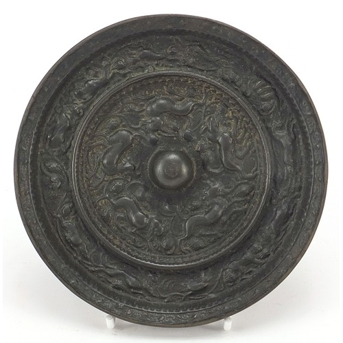 119 - Chinese patinated bronze hand mirror cast with mythical animals and flowers, 14.5cm in diameter