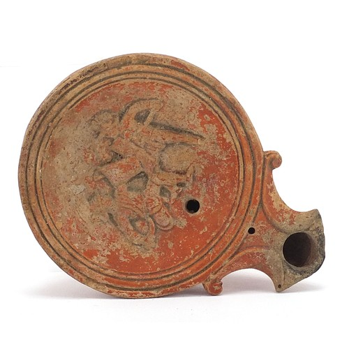 173 - Roman terracotta oil lamp decorated in relief with two figures, 11cm in length