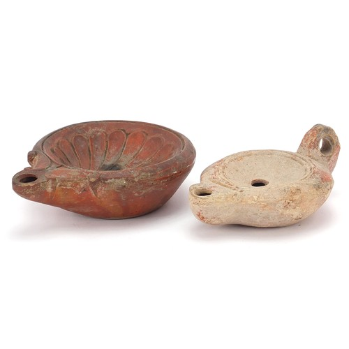 174 - Two Roman terracotta oil lamps, one with handle, the largest 12cm in length