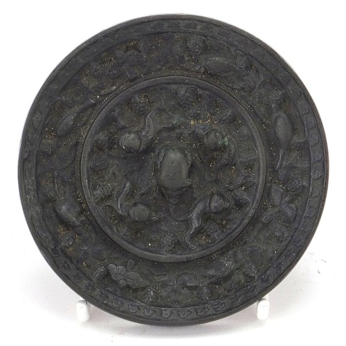 120 - Chinese patinated bronze hand mirror cast with birds of paradise and flowers, 9.5cm in diameter