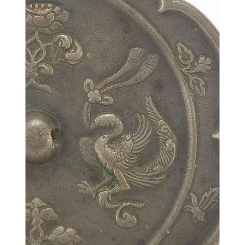 121 - Chinese patinated bronze hand mirror cast with phoenixes and flowers, 15.5cm in diameter