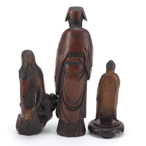 53 - Three Chinese wood carvings including one of an elder and one of standing Buddha, the largest 19.5cm...