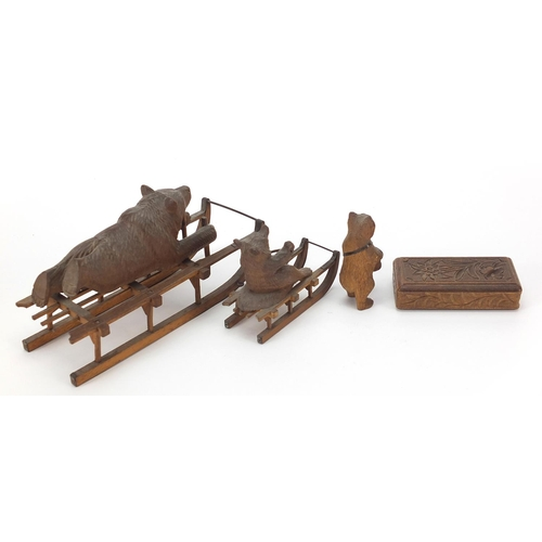 15 - Three carved Black Forest bears and a matchbox including two riding sleds, the largest 15cm in lengt...