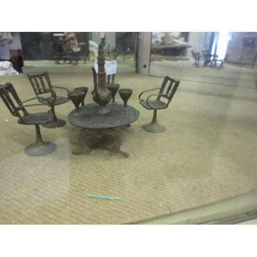 53 - MINIATURE BRASS TABLE AND 4 CHAIR SET WITH GOBLETS AND TEAPOT POSSIBLE DOLLS HOUSE...