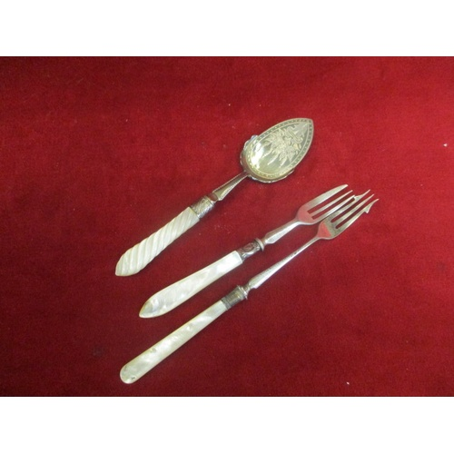 33 - 2 SILVER PLATED PICKLE FORKS AND A PETIT FOURS SPOON ALL WITH MOTHER OF PEARL HANDLES...