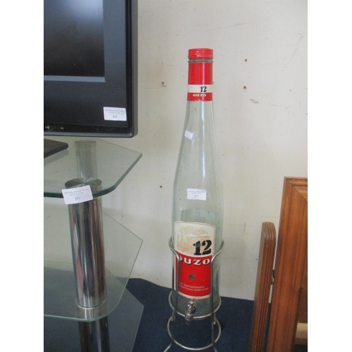 67 - LARGE OUZO BOTTLE WITH TAP  ON METAL STAND...