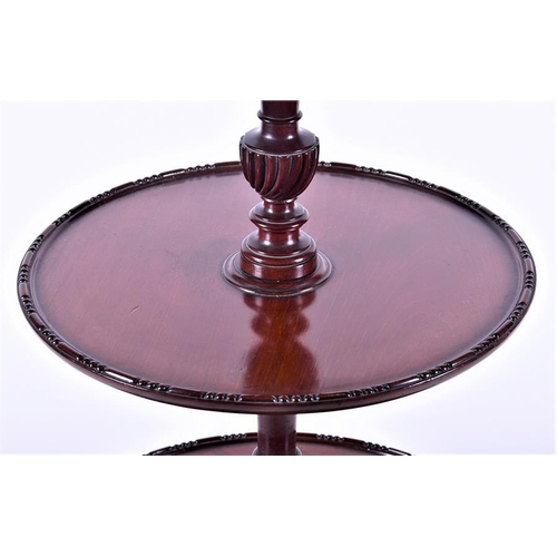 35 - A three tier mahogany whatnot  the graduated circular platforms centred with turned and reeded colum...