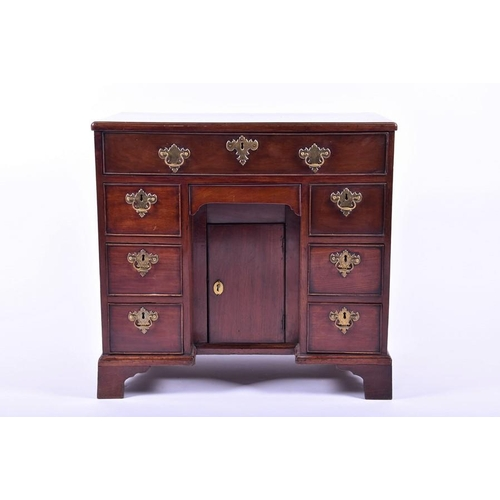 1 - A George II mahogany knee holedesk of small proportions  the rectangular top above an arrangement o...