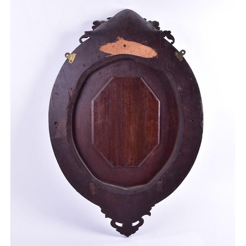 56 - A carved Black Forest oval mirror  designed with scrolled leaves, fruit and small pine cones, the ce...