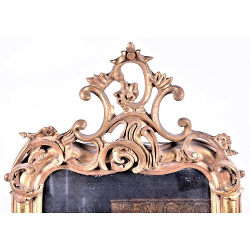 58 - A large Rococo style gilt gesso framed wall mirror  surmounted by scroll motifs, 151 cm x 79 cm (ful...