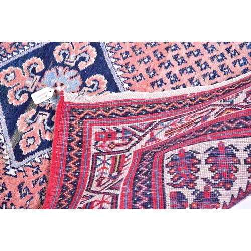 65 - A Persian Qashqai carpet  designed with central indigo diamond medallion against a salmon pink groun...