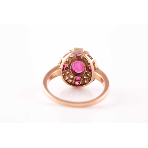 15 - A ruby and diamond cluster ring, the central mixed oval cut ruby with a cruciform plaque of cailbre ...