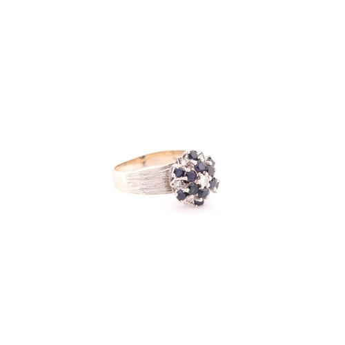 17 - An 18ct white gold, diamond, and sapphire cluster ring, set with a cluster of round-cut sapphires an...