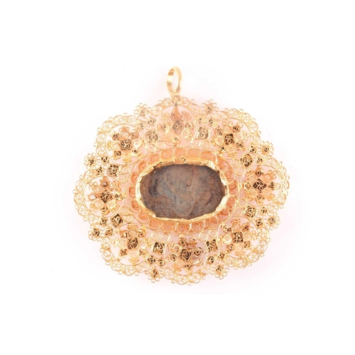 19 - A Catalan gold and garnet pendant, centered with an oval glass aperture with faded paint, within an ...