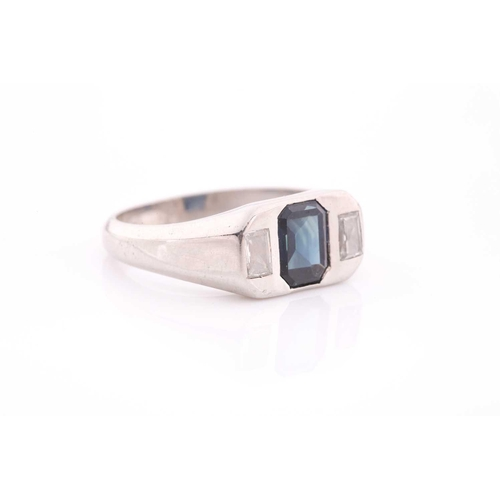 25 - A diamond and sapphire ring, set with a mixed rectangular-cut sapphire, flanked with two modified ba...