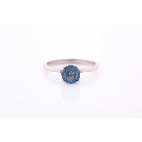 28 - A platinum and solitaire sapphire ring, set with a mixed round-cut blue sapphire of approximately 0....