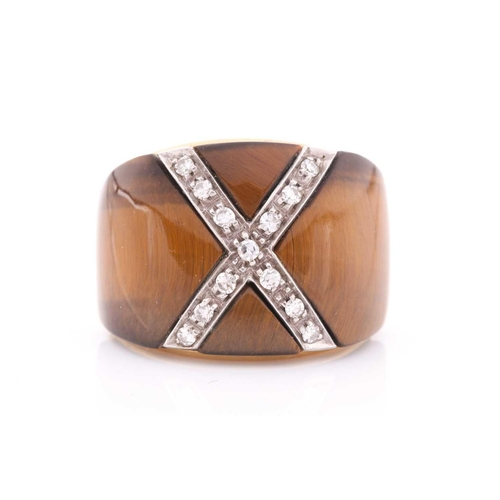 31 - A yellow metal, diamond, and tigers eye cocktail ring, the wide band inset with a diamond-set cross,...