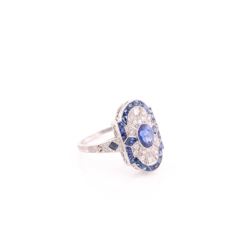 35 - A platinum, diamond, and sapphire plaque ring, in the Art Deco style, centred with a mixed oval-cut ...
