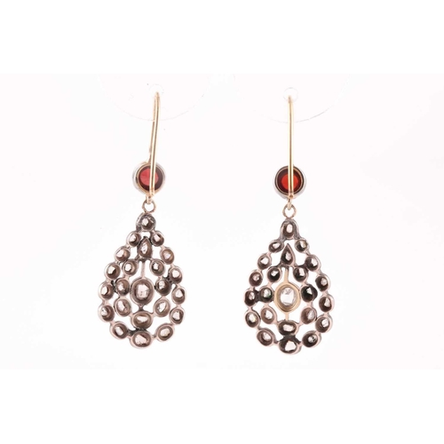 47 - A pair of diamond and garnet earrings, the openwork pear-shaped silver mounts inset with rose-cut di...