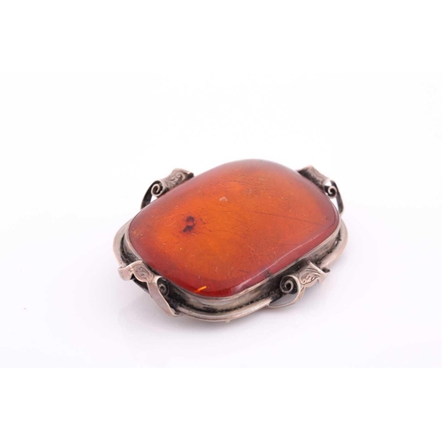 58 - An Art Nouveau silver and amber brooch, the large rectangular single stone amber plaque withing an e...