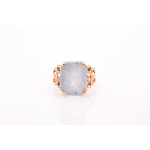 7 - A single stone aquamarine dress ring, the rectangular mixed cut aquamarine in four claw mount to a p...