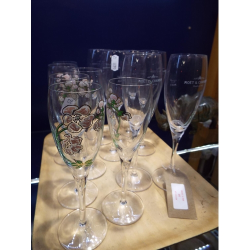 35 - A set of six Moet and Chandon Champagne flutes together with six other flutes enamelled with trailin...