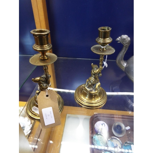 25 - A pair of early 20thC brass figural candlesticks each moulded as gnomes on stylised rocky bases...
