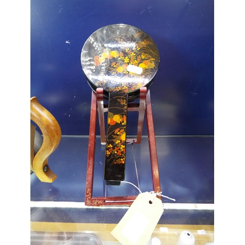 27 - A Chinese floral lacquered mirror on stand...