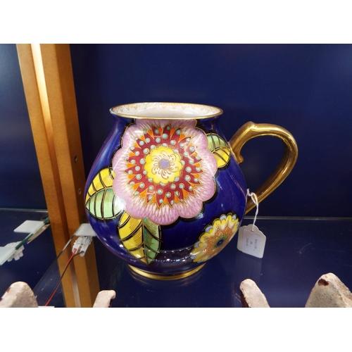 34 - A Carlton-ware blue ground single handled vase having over glazed enamel flower heads painted design...