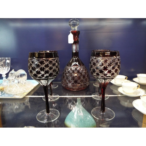 55 - A cut ruby glass decanter and a set of six glasses...