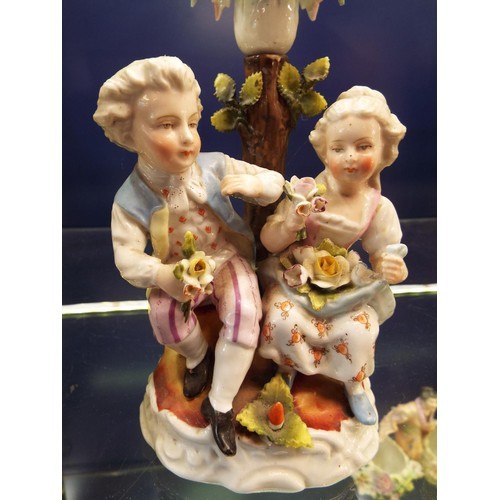 7 - A pair of Meissen figural candlesticks with seated male and female figures...