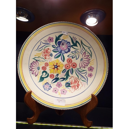 30 - A Poole Pottery charger with floral decoration...