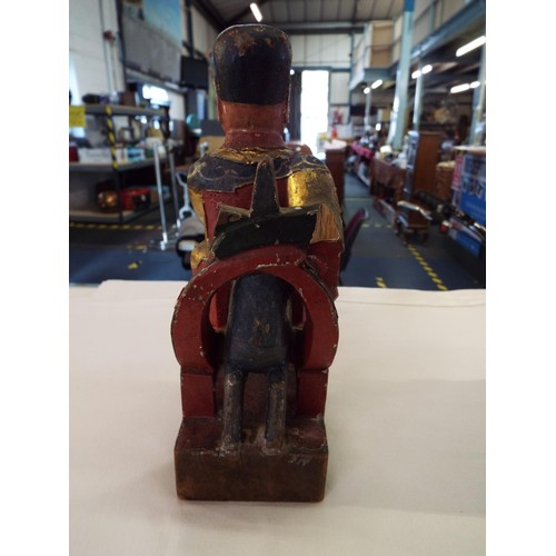 73 - An early 19thC carved wood and gesso figure of a Chinese figure seated on a lion dog (found in the R...