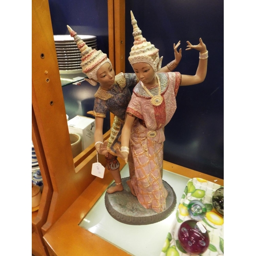 45 - A large Lladro figurine of a Thai male and female dancers in elegant suits of ochre and pink enamels...