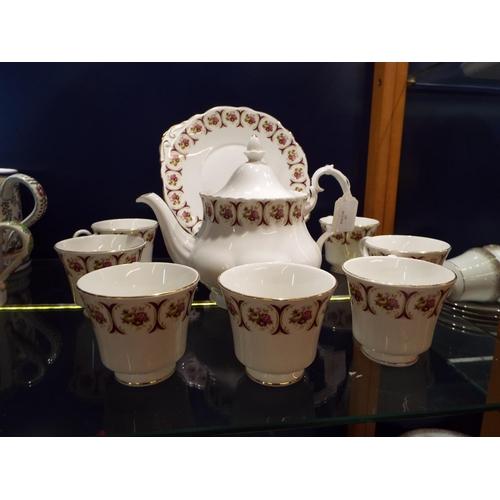 57 - A Berkshire part tea service with floral and gilt design comprising of seven tea cups, tea pot and s...