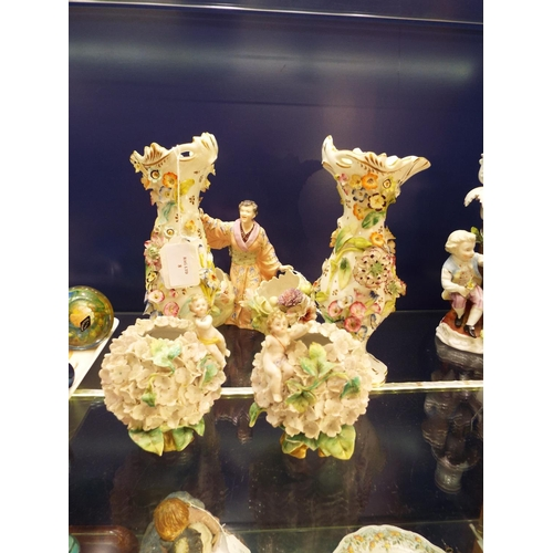 8 - A German porcelain posy vase with Oriental figure between vases encrusted with flowers (hand A/F) an...