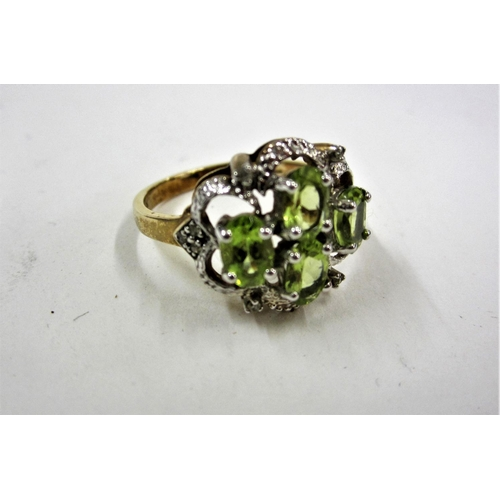 422 - Ladies 9ct Gold Peridot Set Dress Ring in white metal settings with small white stones, pierced & fr...
