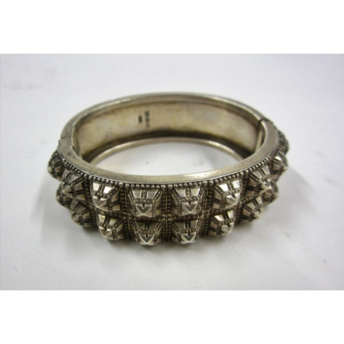 434 - Ladies Hinged Silver Bangle set 18 pyramid style embossed decoration to one side & plain on the othe...