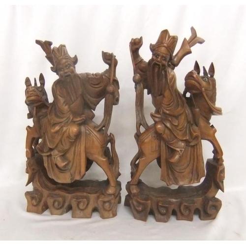 663 - Pair Left & Right Oriental Chinese Hardwood Carvings Deities sitting backwards on horseback, glass e...