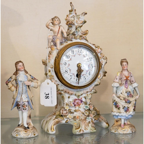 38 - A Continental porcelain mantel clock and a pair of figures:.