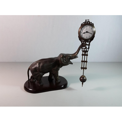 3 - Cast bronze elephant mystery clock on a wooden base, approx 10'' x 9'' overall...