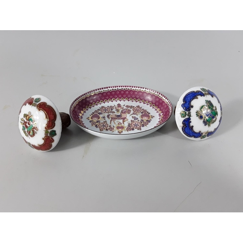 10 - Decorated enamel dish and 2 matching bottle stoppers...