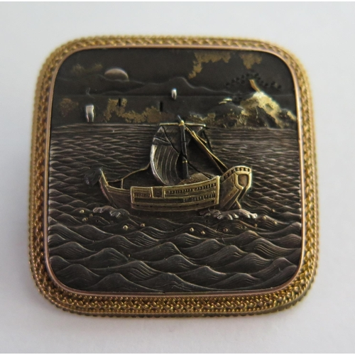 260A - A Japanese Meiji Period Shakudo Brooch decorated with a scene sailing vessel with erupting volcano t...