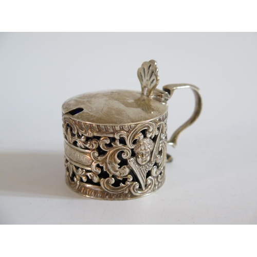 19 - A Victorian Silver Mustard Pot with pierced foliate and cherub decoration, London 1895...