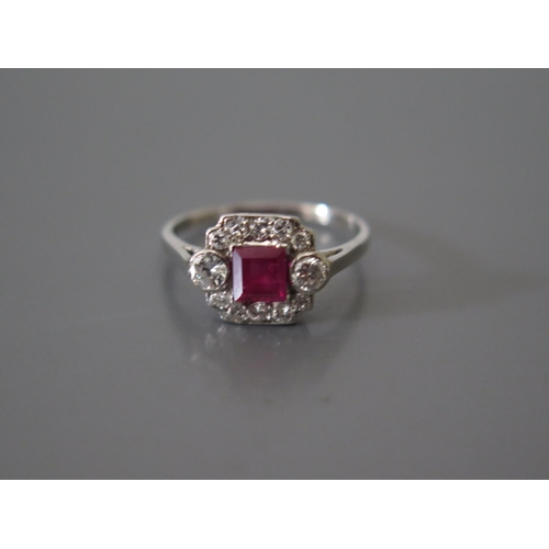 200d - A Ruby and Diamond ring in a precoius white metal setting (ruby c. .83ct)...
