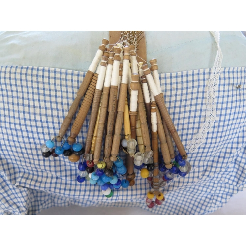 256 - A Lace Maker's Pillow with one named bone bobbin, two others and wooden bobbins...