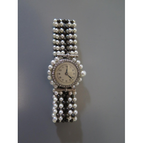 187 - A Diamond Mounted Evening Watch with pearl strap...
